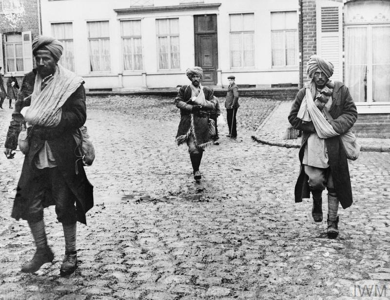 A group of wounded Indian Army soldiers walk across the cobbles of a French village