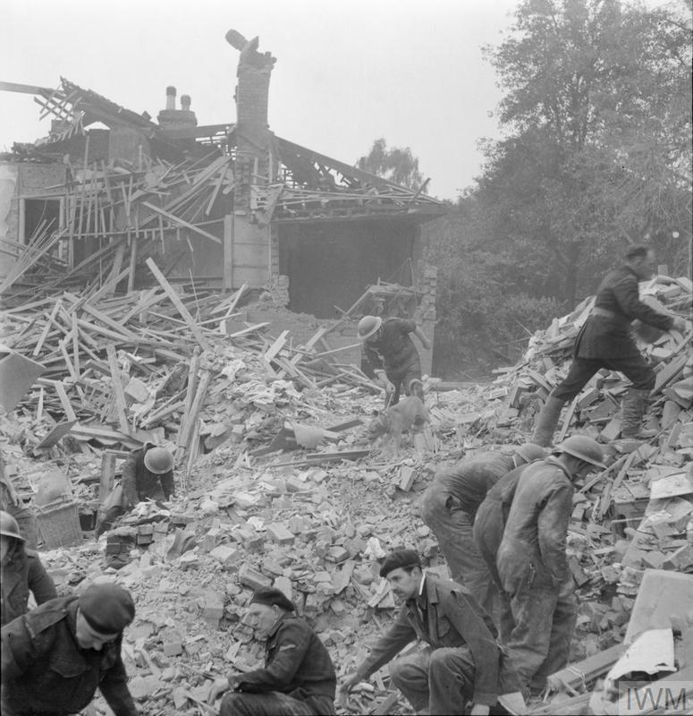 Civil Defence rescue workers search amid piles of rubble as they try to dig survivors out of collapsed buildings following a V1 attack in the Highland Road and Lunham Road area of Norwood, London, SE19. One is using a dog to help in the search. In the background, a half-destroyed house can be clearly seen.