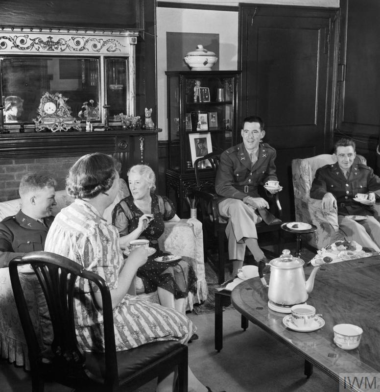 Lieutenant Loren Bacon (from Eugene, Oregon), Lieutenant Chas Raymond (from New York) and Lieutenant J T Crane (from Chicago) take tea in the home of Mrs A D Weller (left) in Winchester, Hampshire.