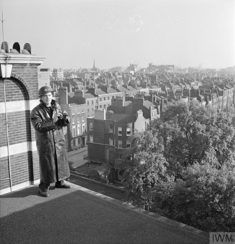 Clive W Black is the house steward at the Royal Academy of Music. He helped to organise the Academy's ARP provision, and can be seen here acting as a fire watcher on the roof of the Academy. A good view of the local area can be seen from the roof. The original caption states that Mr Black is also responsible for stage lighting and any electrical work at the Academy.