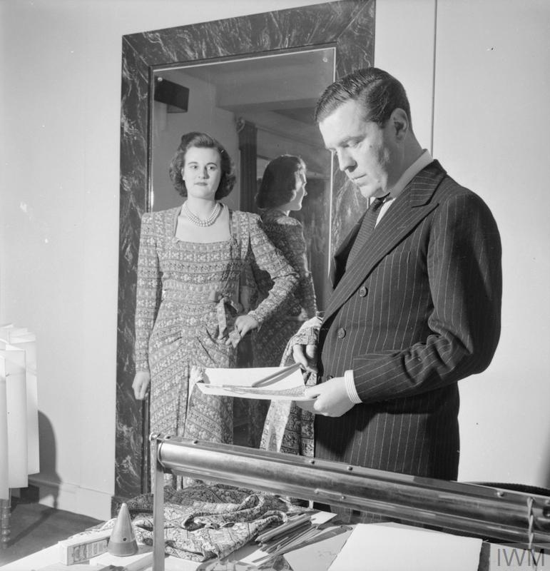 Fashion designer Norman Hartnell compares a finished garment to his original sketch and fabric sample at his studio in 1944.