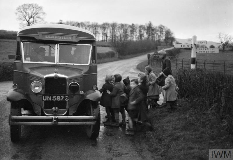 Children queue to get on a bus, Shropshire, 1944