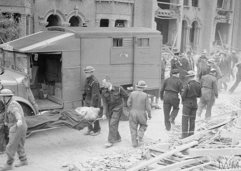 A casualty is carried by Civil Defence stretcher-bearers past an ambulance of the American Ambulance Great Britain following a devastating V1 attack in the Highland Road and Lunham Road area of Upper Norwood. In the background, other Civil Defence workers can be seen as they work to clear the rubble, timbers and debris from the road, and collect more casualties.