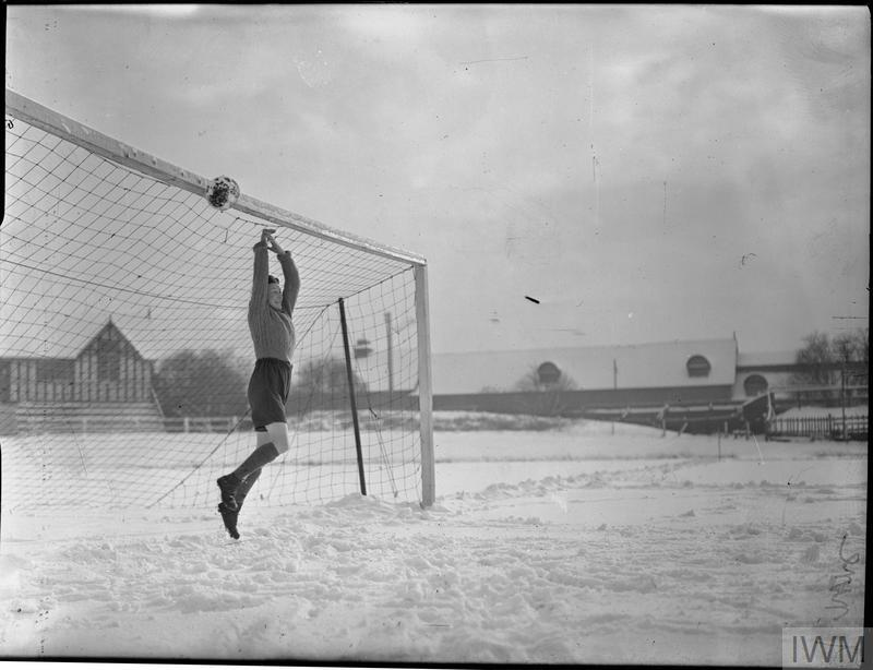 During a football match between teams from the Fairey and AV Roe aircraft factories, Fairey goal keeper Betty Stanhope destroys any hope of a score for the AV Roe team, as she knocks the ball up to hit the cross bar. The match is taking place on a snow-covered pitch at the Manchester Athletic Club ground at Fallowfield.
