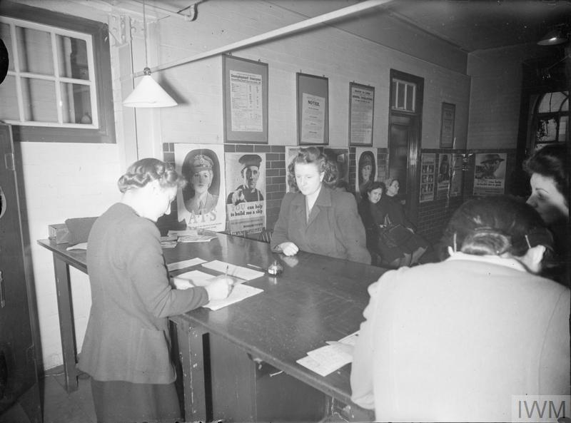 SIXTEEN YEAR OLDS REGISTER: TEENAGERS RECEIVE THEIR ADULT ID CARDS AT THE LABOUR EXCHANGE, LONDON, ENGLAND, UK, 1945