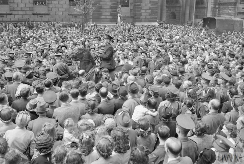 A mounted London policeman pushes his way through the crowds of people gathered in Whitehall, London, to hear Churchill's Victory speech and to celebrate Victory in Europe Day. The policeman is trying to clear a path through the crowds to allow traffic to get through. The crowd is a mix of service personnel, including Grenadier Guards and members of the Home Guard, and civilians, including children. A soldier can be seen at the top of a bus stop in the background of the photograph.