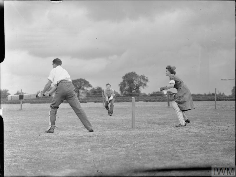 Nurse P A Taylor (from Cricklewood) plays wicket keeper for Sergeant P W Reeves (left, batting) and Leading Seaman M Pierrepoint (centre, fielding) during a game of cricket in her lunch hour at the Robert Jones and Dame Agnes Hunt Orthopaedic Hospital, Oswestry. The original caption states that Sgt Reeves is from Lowestoft and was wounded in the right arm when descending over Normandy. Leading Seaman Pierrepoint is from East Sheen, near Richmond in Surrey.