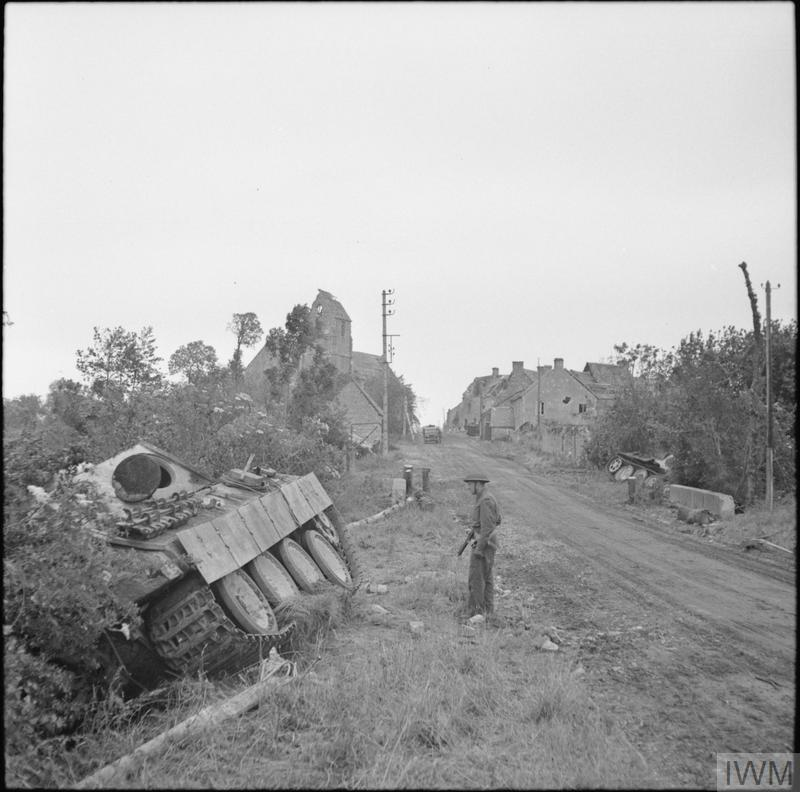 A knocked-out German Panther tank lies at the side of a road in Normandy in 1944.