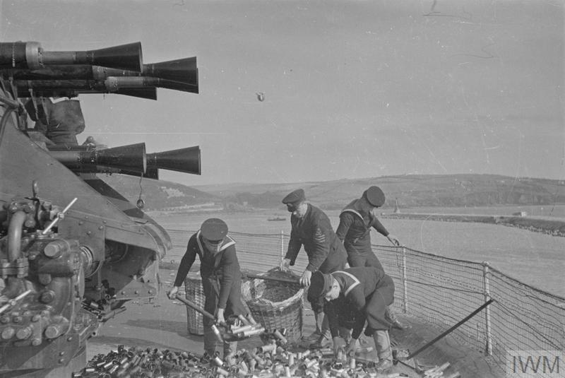"""GUNNERY TRAINING. 3 OCTOBER 1940, BREAKWATER FORT, AT THE ENTRANCE TO PLYMOUTH SOUND. THE FORT IS ONE OF THE ONLY TWO PLACES WHERE SAILORS CAN, AFTER LEARNING THE THEORY OF GUNNERY, FIRE """"LIVE"""" AMMUNITION BEFORE PASSING OUT AS QUALIFIED ANTI AIRCRAFT GUNNERS. HERE THEY FIRE AT A DRONE, WHICH IS A LONG BAR TOWED BEHIND AN AEROPLANE. THEIR EFFORTS BEING RECORDED BY ELECTRICAL APPARATUS INCLUDING A CAMERA WHICH SHOWS WHERE THEIR AIM WAS."""