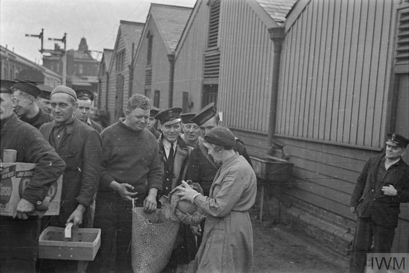 "VEGETABLES FOR MINESWEEPERS. 1940, ONCE A MONTH THE FARMERS OF ESSEX BRING ALL THEIR SURPLUS VEGETABLES TO A NAVAL PORT WHERE THEY ARE HANDED OUT TO MINESWEEPING TRAWLERS. THE COLLECTION AND STORAGE OF THE VEGETABLES IS ARRANGED BY THE WVS, AND THE CREWS OF THE MINESWEEPERS SIMPLY COME DOWN TO THE WVS DEPOT AT THE QUAYSIDE AND ASK FOR WHATEVER THEY WANT, CARROTS, POTATOES, CABBAGES AND EVEN FLOWERS. ON THURSDAY MORNINGS THE CREW OF MINESWEEPING TRAWLERS AT THIS PORT COME DOWN TO THE ""COMFORTS"" DEPOT AT THE QUAY, BRINGING WITH THEM ANY SACKS OR BOXES THEY CAN LAY THEIR HANDS ON."