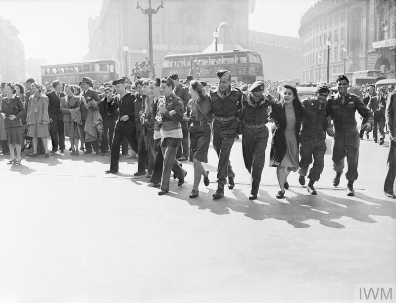 In London's Piccadilly Circus,a group of servicemen and women, and a civilian woman, link arms as they walk towards the camera, singing as they dance in celebration around Eros (not pictured), on the news that the war in Japan is over. Behind them, crowds of people are gathered in the sunshine. Several buses can also be seen. This photograph was taken from beside Eros, looking towards Piccadilly (left) and Regent Street (right).