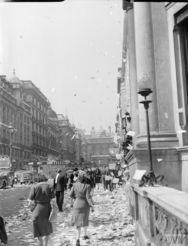 Civilians walk amongst the piles of torn up paper which have been thrown, 'ticker tape'-style, from the windows of offices, on Lower Regent Street, London, to celebrate the signing of the Peace with Japan, 15 August 1945. More paper can be seen fluttering down onto the pavement and road: many vehicles appear to have stopped. It appears that this photograph was taken on Lower Regent Street, looking back up towards Piccadilly Circus. In the middle of the road, a brick surface shelter can be seen.