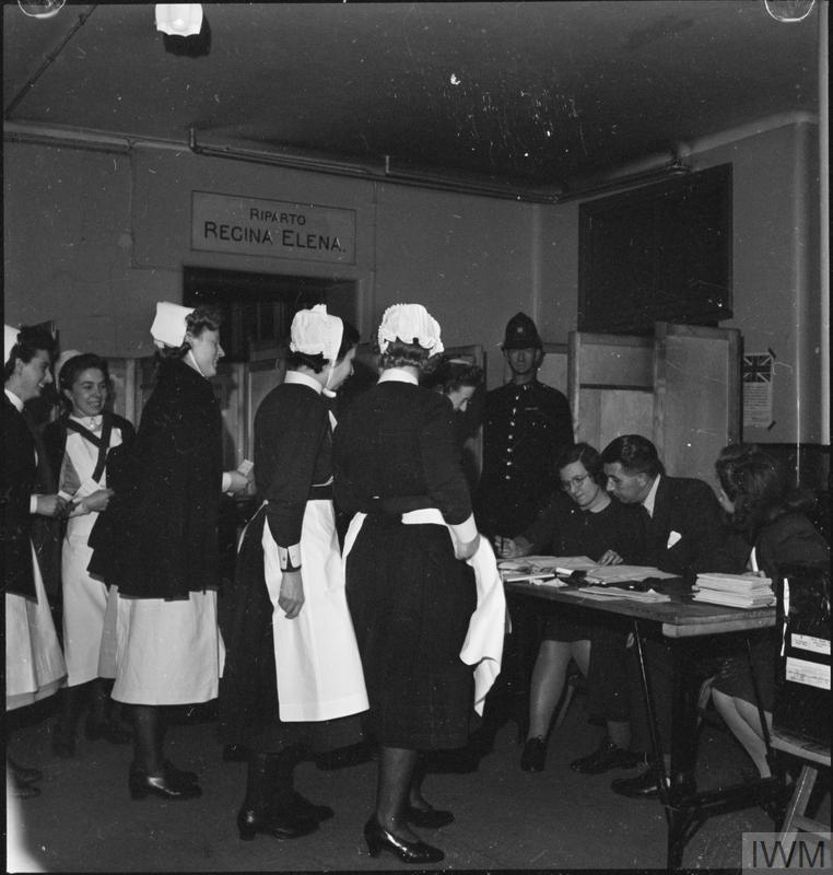 Nurses in uniform queuing in front of a table at a polling station waiting for their ballot papers. © IWM D 25103