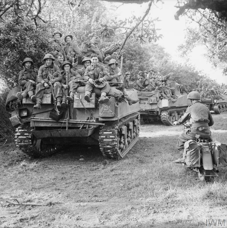 Sherman tanks of the Staffordshire Yeomanry, 27th Armoured Brigade, carrying infantry from 3rd Division, move up at the start of Operation 'Goodwood', 18 July 1944.