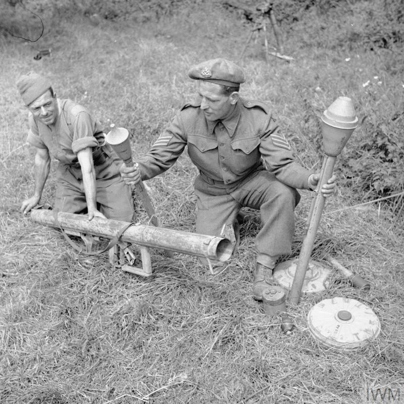 Instructors at a 59th Division school for potential NCOs at Vienne-en-Bessin demonstrate various German anti-tank weapons, including a Panzerschreck, two types of Panzerfaust and anti-tank mines, 1 August 1944.