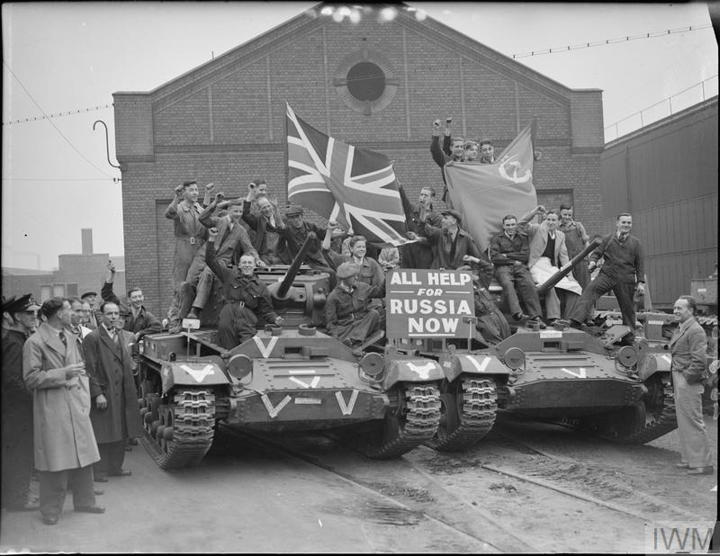 """Factory workers ride on Valentine tanks as they leave a factory in Smethwick. A notice propped on the front of the tanks reads """"All Help for Russia Now"""". The workers are holding a Union flag and a Russian flag and many have their fists raised in a Communist salute."""
