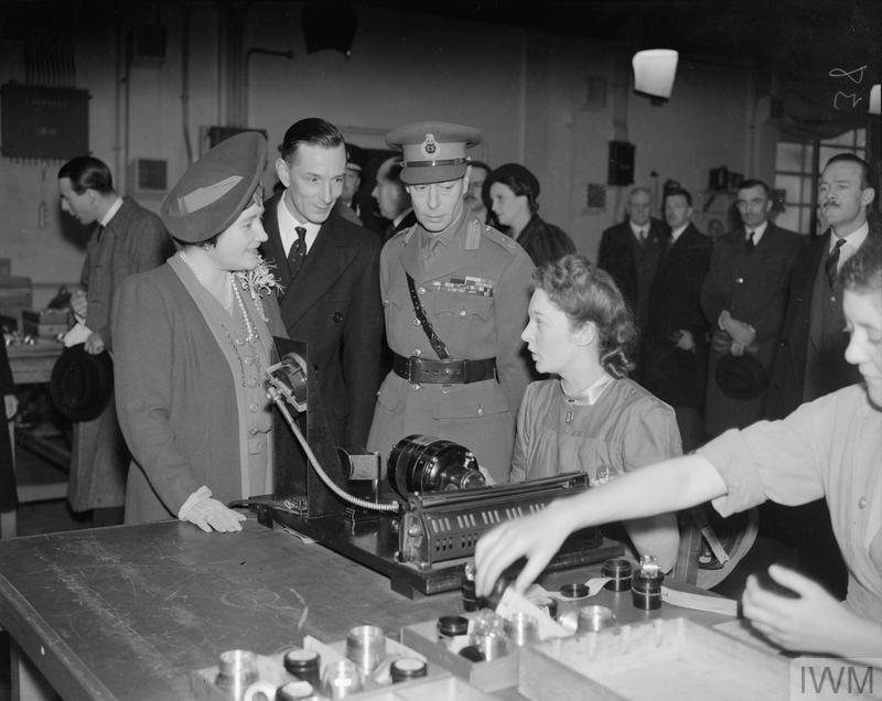 HM King George VI and HM Queen Elizabeth talk to a woman operating a fuse testing machine during a visit to the Royal Ordnance factory in Blackburn. Factory superintendent Stephen van Ryssen escorts them.