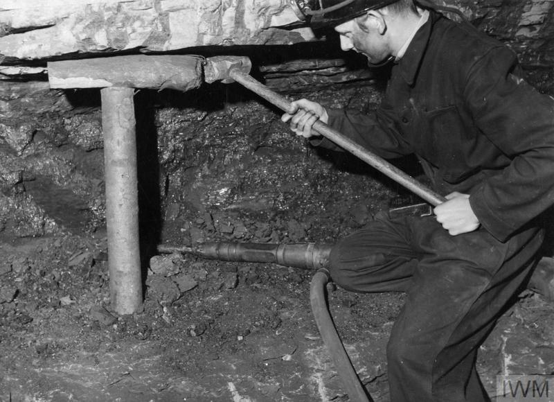 'Bevin Boy' Hubert Claud Morgan, aged 18, drives in a roof support at the coal face, during his training at a colliery near Canterbury. According to the original caption, Hubert was a clerk for Hastings Education Authority before being balloted as a 'Bevin Boy'.