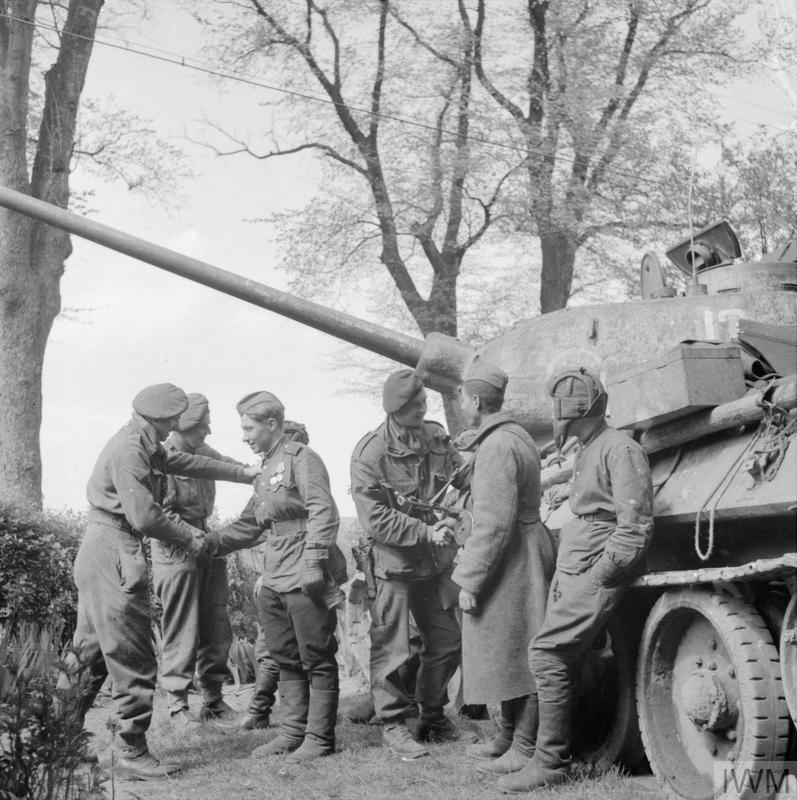 Men of 6th Airborne Division greet the crew of a Russian T-34/85 tank during the link-up of British and Soviet forces near Wismar on the Baltic coast, 3 May 1945.
