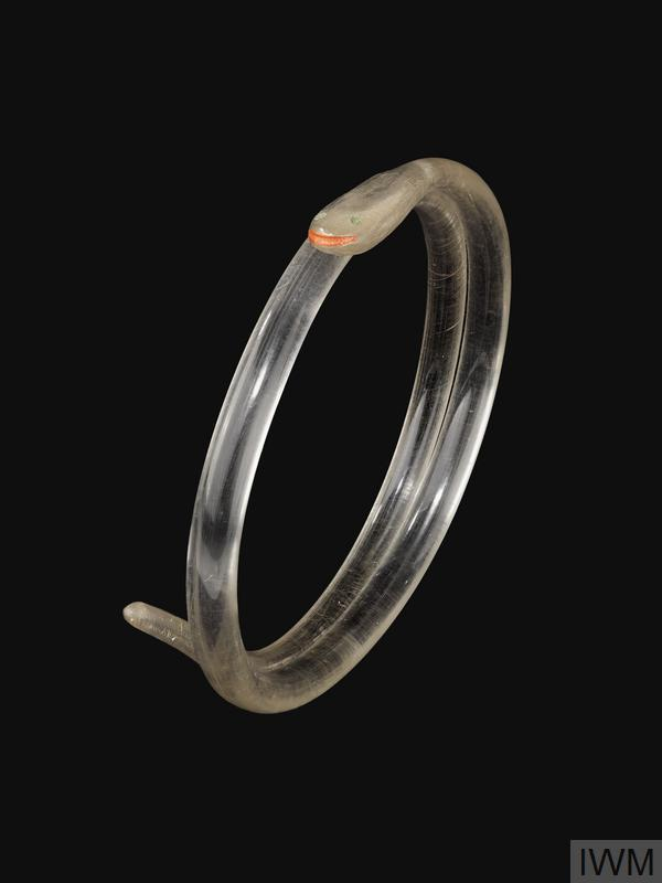 bracelet A coil of plastic with one end slightly flattened and inscribed and painted to represent a snake.