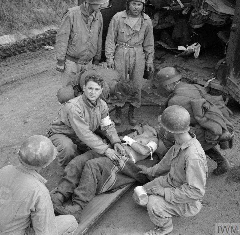 US Army and captured German medics attend to a wounded German soldier, 6 February 1944.