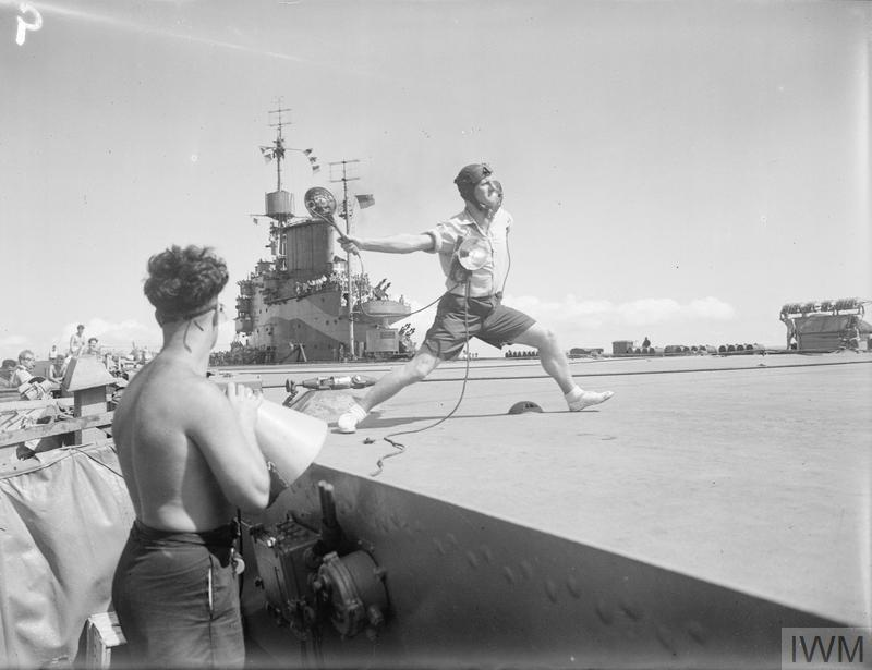 """THE """"BATSMAN"""" ON HMS ILLUSTRIOUS. JANUARY 1943, ON BOARD HMS ILLUSTRIOUS IN THE INDIAN OCEAN, THE LANDING ON AND TAKING OFF OF ALL AIRCRAFT FROM A CARRIER IS MAINLY THE RESPONSIBILITY OF THE LIEUTENANT FLYING WHO WORKS UNDER THE DIRECT ORDERS OF COMMANDER(FLYING). THE LIEUTENANT FLYING IS KNOWN AS THE BATSMAN. THE SAFETY OF ALL PILOTS AND AIR CREWS IS LARGELY DEPENDANT ON THE PILOT FOLLOWING IMPLICITLY THE SIGNALS GIVEN HIM BY THE BATSMAN. AN OFFICER WITH MANY FLYING HOURS AND EXPERIENCE OF DECK LANDINGS, HE KNOWS JUST WHEN A PILOT IS MAKING THE WRONG APPROACH WHICH WILL LEAD TO A BAD LANDING AND POSSIBLY A CRASH, AND SIGNALS HIS INSTRUCTIONS TO THE PILOT ACCORDINGLY. THE COMMANDER FLYING, WHO IS ALWAYS ON THE FLYING BRIDGE DURING ANY OPERATIONS, MAY CONSIDER CONTRARY TO THE BATSMAN, THAT A PILOT IS MAKING A WRONG APPROACH AND IF NECESSARY CAN FIRE A ROCKET FROM THE BRIDGE AND SEND THE PILOT ROUND AGAIN FOR ANOTHER APPROACH."""