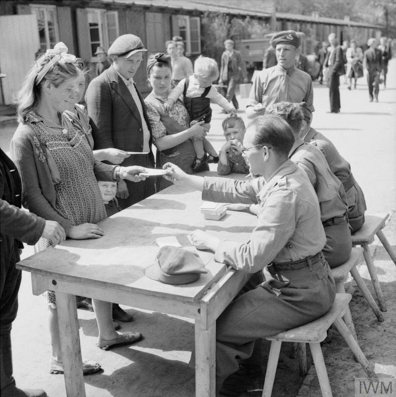 A Displaced Persons camp in the grounds of Hamburg zoo. People queue to register at a table.
