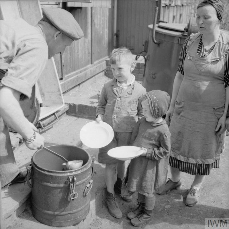 © IWM BU 6635 Two Polish children, Leon and Janina Waszczuk, are given soup soon after their arrival at No.17 Displaced Persons Assembly Centre located in Hamburg Zoological Gardens. Their mother Władysława is behind them.