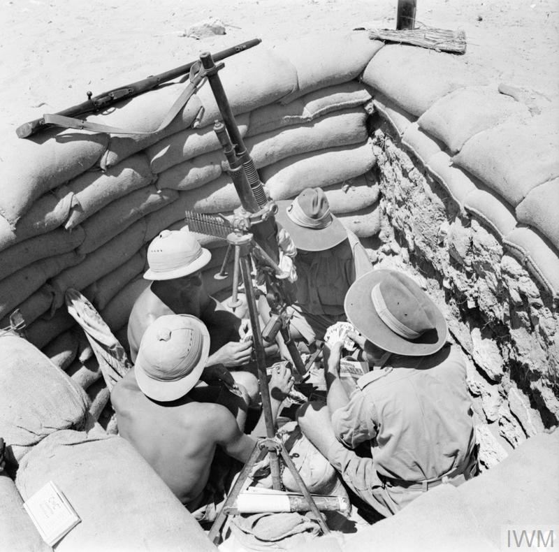 Easily identified by their distinctive headgear, South African and Australian soldiers enjoy a game of cards in a gun pit.