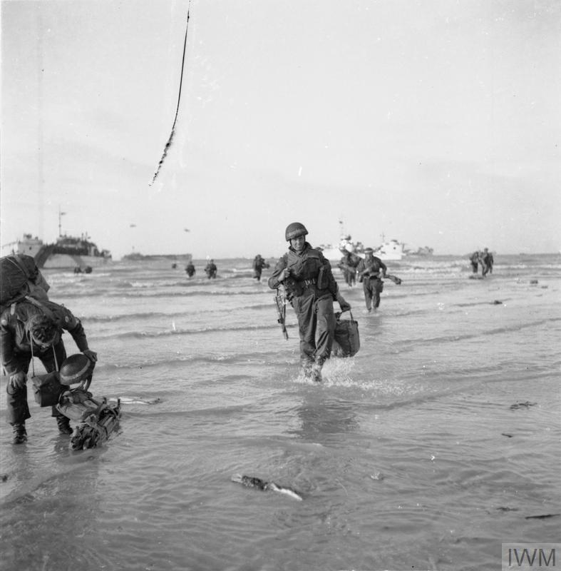 Beach Group troops wade ashore from landing craft on Queen beach, Sword area, on the evening of 6 June 1944.
