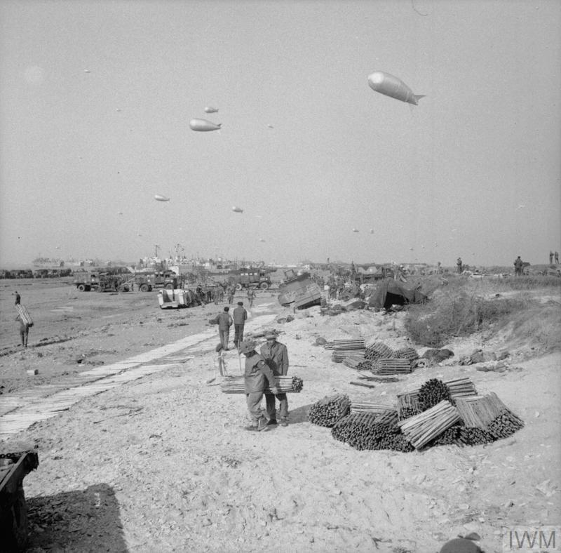 Vehicles and supplies coming ashore, with barrage balloons above the beach, Gold area, 7 June 1944.