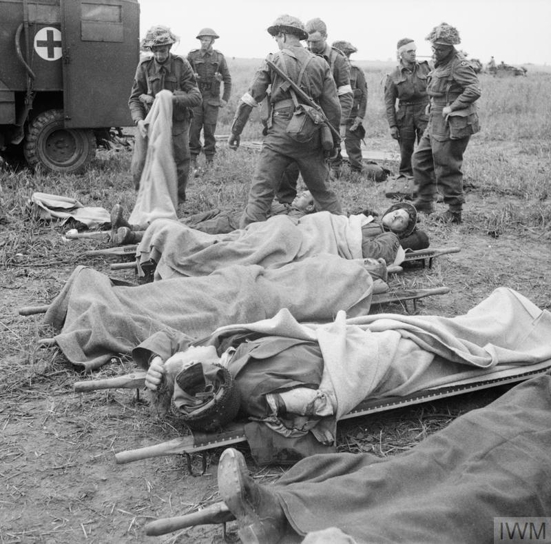 Casualties on stretchers awaiting transport to a casualty clearing station during Operation 'Epsom', 26 June 1944.