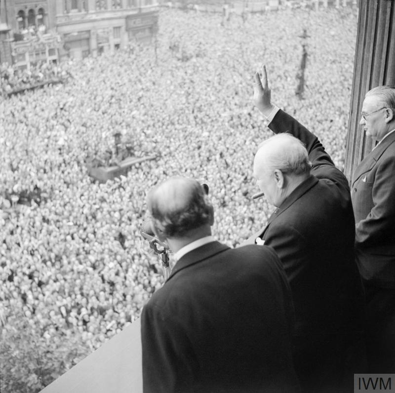 Churchill waving to crowds in Whitehall, London, as they celebrate VE Day, 8 May 1945.