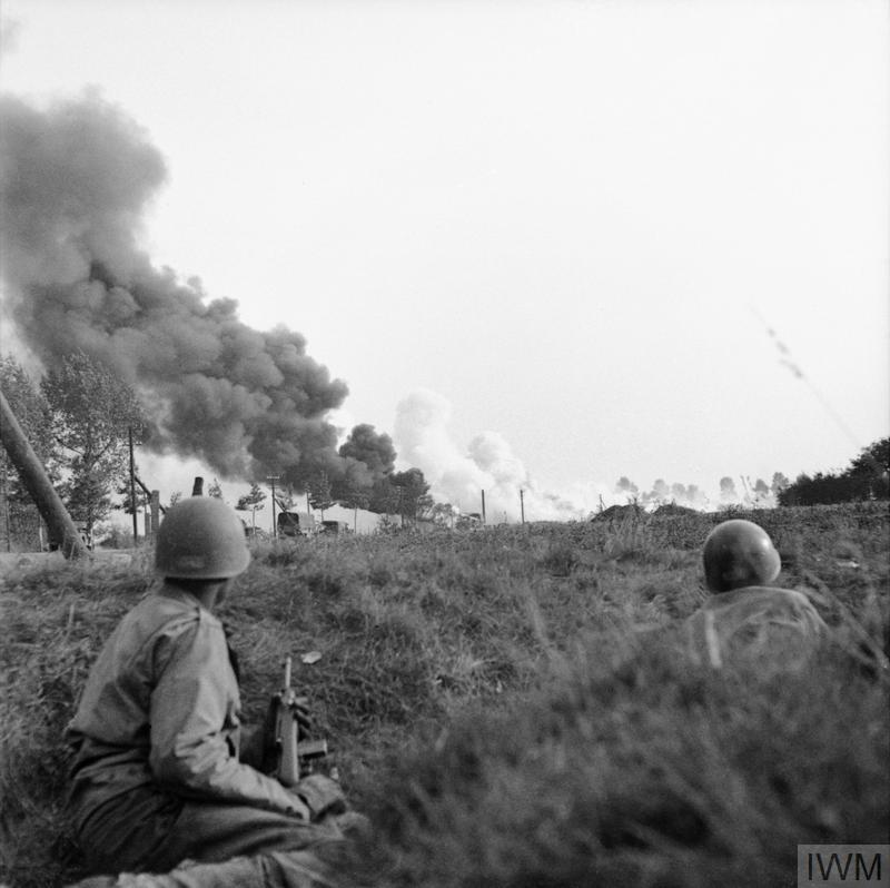 A convoy of lorries under enemy artillery and mortar fire on the road between Son and Eindhoven, 20 September 1944. In the foreground American paratroopers shelter in a ditch.