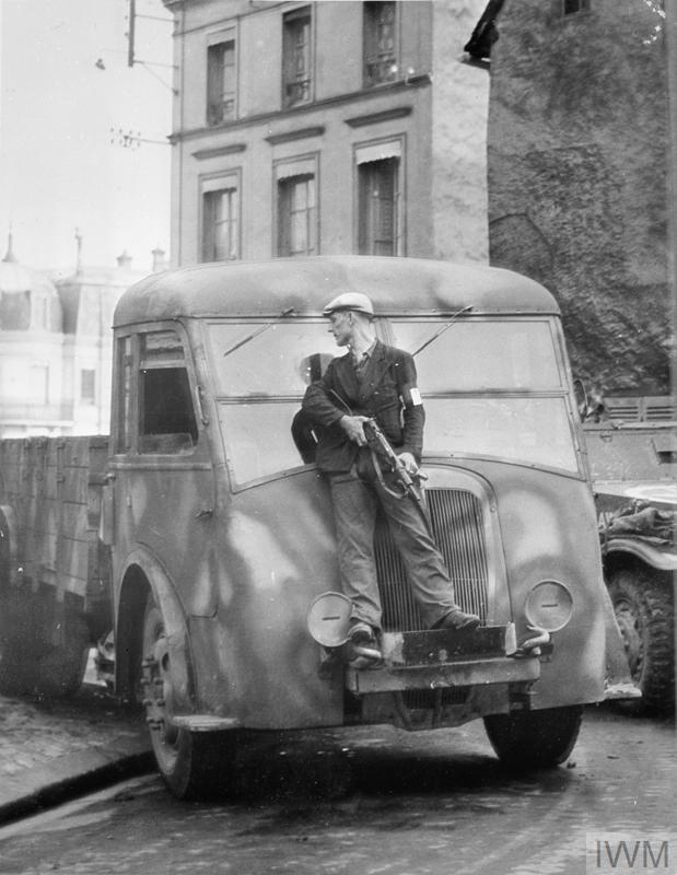 A member of the French Forces of the Interior (FFI) uses a truck for cover during gun battles with German snipers in Dreux, August 1944. During this period several French towns were liberated by the FFI in advance of Allied forces.
