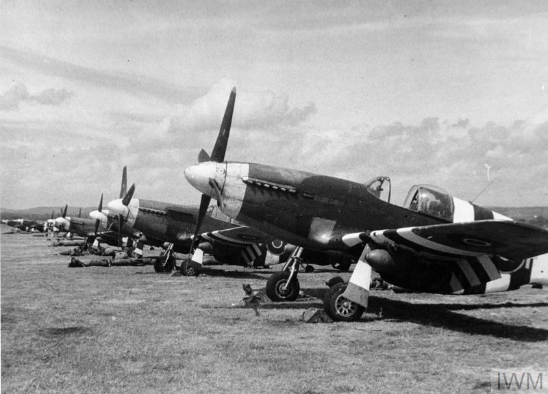 North American Mustang Mark IIIs of No. 129 Squadron RAF, loaded with a 250-lb MC bomb under each wing, lined up at Coolham, Sussex.