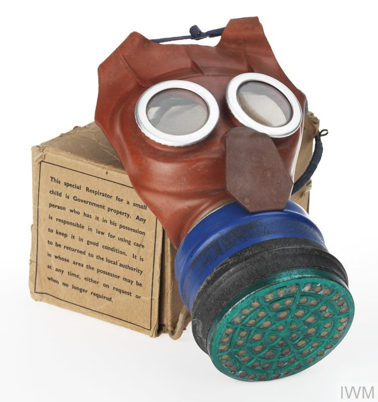 respirator red rubber mask; clear round eyepieces with steel surrounds crimped around edges of lenses which protrude from front of mask; exhale flap protrudes from front nose area; mask tapers towards opening at bottom, into which is inserted the canister (filter) which is then secured with a metal clamping ring covered by clear tape; canister is painted royal blue with the perforated base in light metallic green and 2 lines of black tape wound around it.