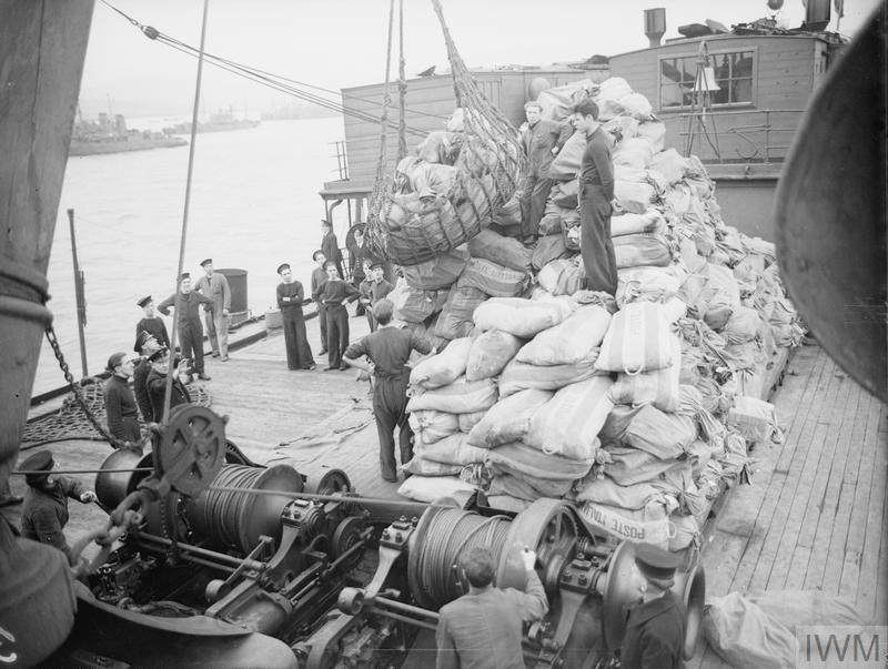 FIRST MAIL OUT OF ITALY. OCTOBER 1943, SCAPA FLOW. SEVERAL HUNDRED BAGS OF MAIL ARRIVED IN THE UNITED KINGDOM FROM LIBERATED ITALY. THEY INCLUDED LETTERS FROM BRITISH TROOPS AND LETTERS FOR ITALIANS IN THE COUNTRY. THE WERE BROUGHT HERE BY ONE OF HM SHIPS AND WERE HANDLED ON ARRIVAL BY THE FLEET MAIL OFFICE.