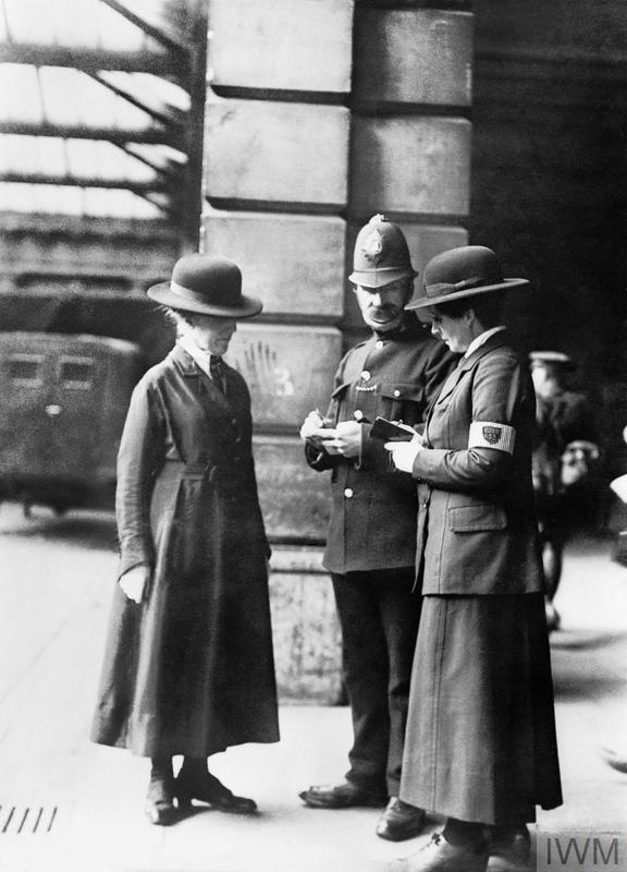 Two members of the Women's Police Service comparing notes with a male police constable at Euston Station, London, 1918