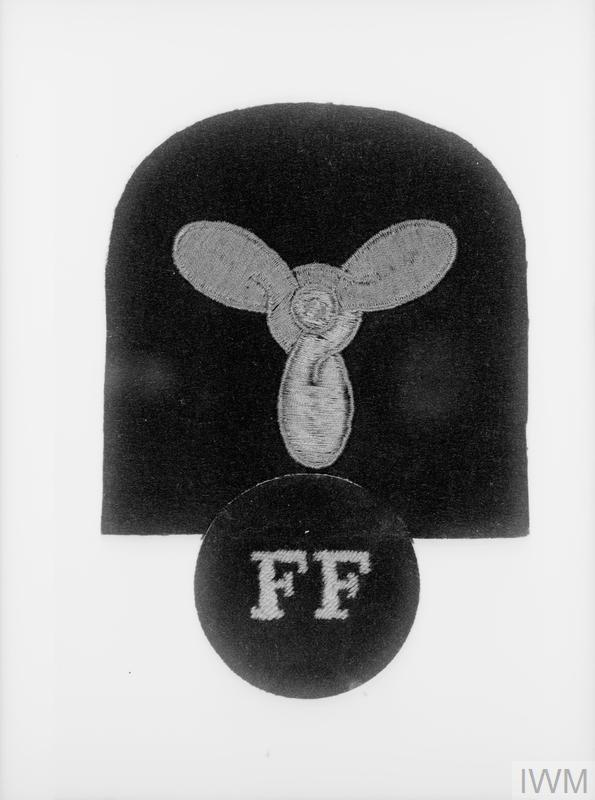 NAVY FIRE FIGHTERS BADGE. 23 OCTOBER 1943. THE ROYAL NAVY NOW HAS ITS OWN PERMANENT FIRE FORCE AND THIS BADGE HAS BEEN APPROVED FOR WEAR BY RATINGS MEMBERS. THE BADGE CONSISTS OF A PROPELLER WITH THE LETTERS F F BELOW.