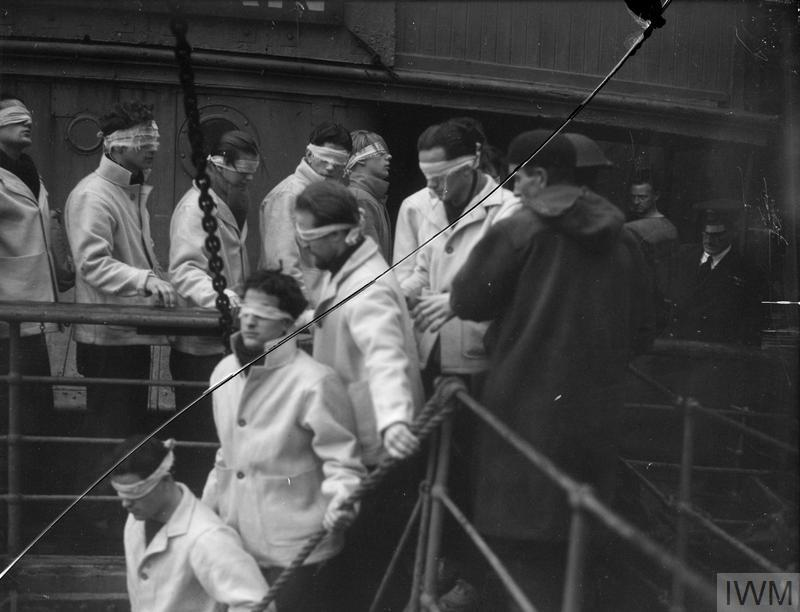 Blindfolded SCHARNHORST survivors, in merchant seaman rescue kit, being landed on their way to internment.