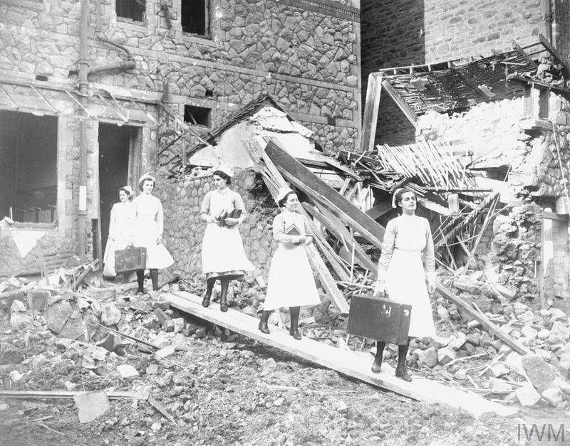 Nurses leaving the wrecked nurses home of the Royal Infirmary, Cardiff, with their salvaged possessions, following German air attack.