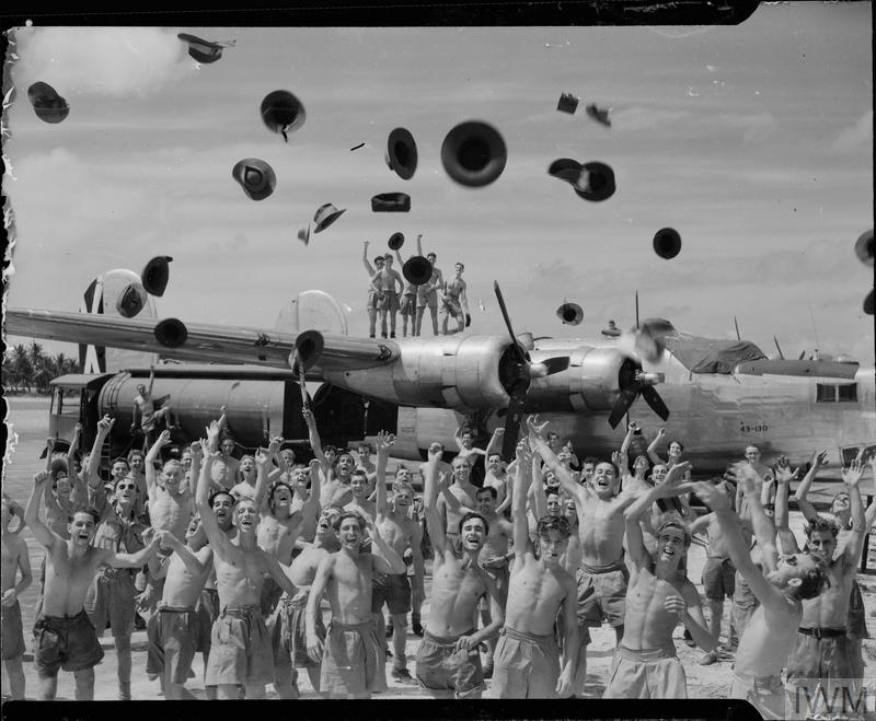 Ground crews of No.356 Squadron RAF based at the Brown's West Island, Cocos Islands, celebrate in front of one of their Consolidated Liberator Mark B VIs on hearing the news of the surrender of Japan.