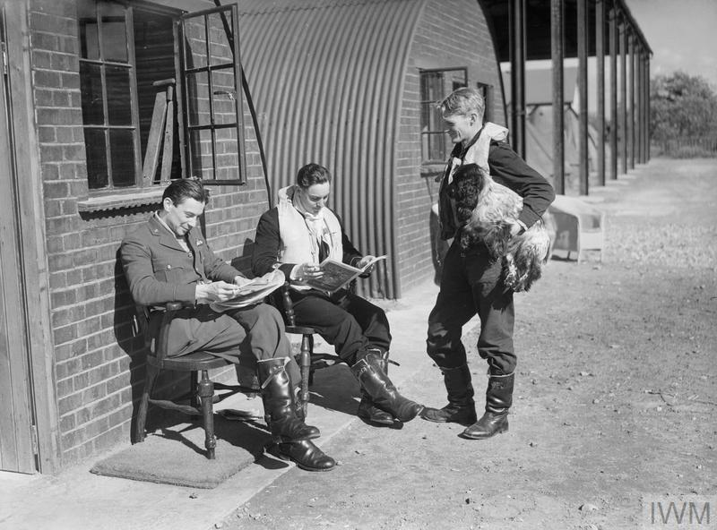 "Pilots of No. 19 Squadron RAF relax between sorties outside their crew room at Manor Farm, Fowlmere, Cambridgeshire. They are (left to right), Pilot Officer W Cunningham, Sub-Lieutenant A G Blake of the Fleet Air Arm (nicknamed ""The Admiral"") and Flying Officer F N Brinsden, with Spaniel. Blake was killed the following month in a dogfight over Chelmsford, Essex."