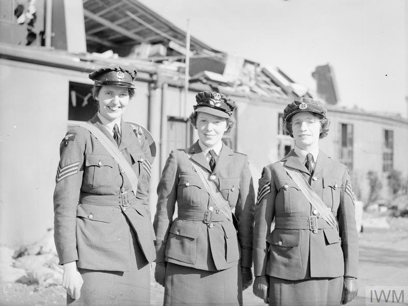 Sergeant Joan E Mortimer, Flight Officer Elspeth C Henderson and Sergeant Helen E Turner, recipients of the Military Medal for gallantry, standing outside damaged buildings at Biggin Hill, Kent. All three were WAAF teleprinter operators who stayed at their posts and continued to work the defence lines during the heavy Luftwaffe attacks on Biggin Hill on 1 September 1940.