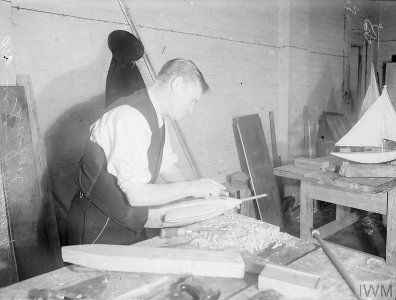 AT A NAVAL HOSPITAL IN CHESHIRE. 20 NOVEMBER 1944, ROYAL NAVAL AUXILIARY HOSPITAL, CHOLMONDLEY CASTLE, CHESHIRE. SICK MEN OF THE ROYAL NAVY AND ROYAL MARINES NOW ON THE ROAD TO RECOVERY, ARE SPENDING THE TIME MAKING CHRISTMAS TOYS AND GIFTS FOR THEIR OWN CHILDREN AND FOR VARIOUS HOSPITAL AND NAVAL CHARITIES.