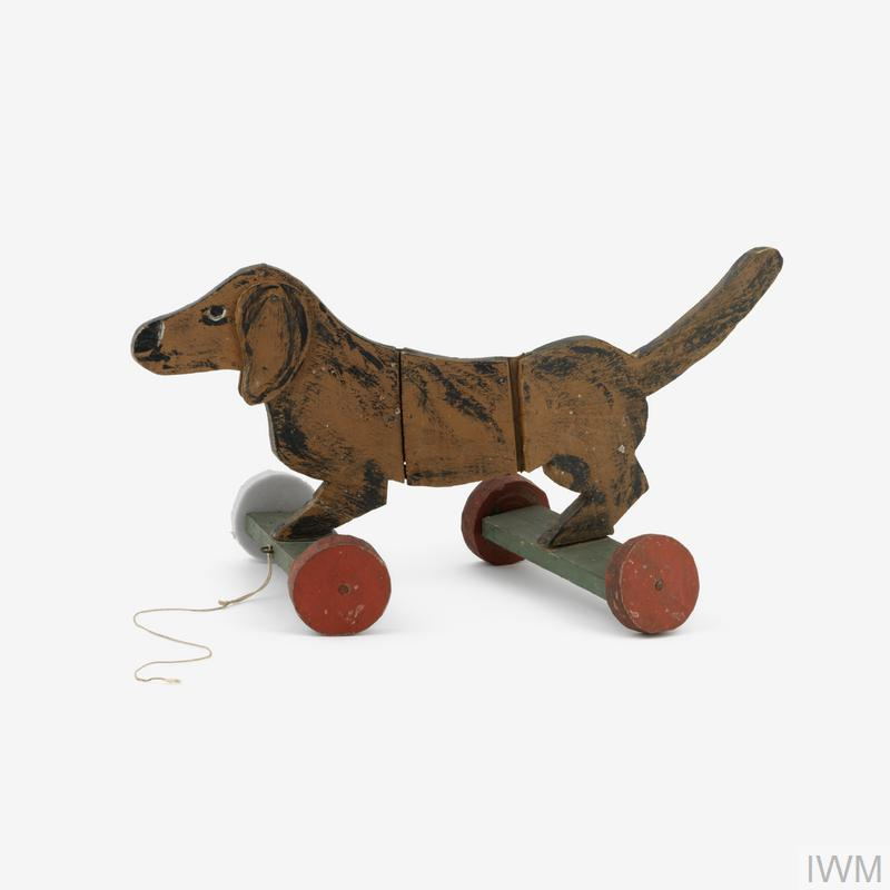 Pull-along toy dog (Daschund), comprising a flat wooden cut-out dog mounted on four wheels