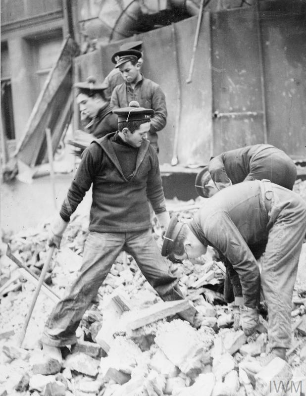 Free French sailors help salvage belongings amid the wreckage of a blitzed building in Portsmouth, 14 January 1941