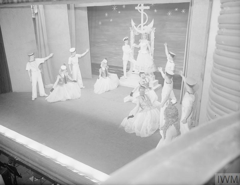 """""""PACIFIC SHOW BOAT"""". 12 JUNE 1945, LYRIC THEATRE, HAMMERSMITH. THE ALL-NAVY SHOW """"PACIFIC SHOW BOAT"""" WHICH IS BEING SENT BY AMENITIES SHIP TO THE PACIFIC TO ENTERTAIN PERSONNEL OF THE BRITISH PACIFIC FLEET AFTER ITS LONDON RUN. COSTUMES AND DECOR ARE BY SUB LIEUTENANT HEDLEY BRIGGS AND THE MUSICAL NUMBERS BY LIEUTENANT RONNIE HILL."""