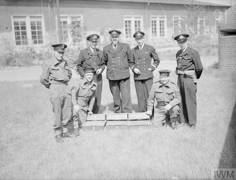 NAZI ESPIONAGE GOLD CAPTURED BY NAVAL PARTY. 23 MAY 1945, ECKENFORDE, GERMANY. LIEYT CDR THOMAS SKERRIN RNVR, OF POOLE, DORSET LED A SMALL PARTY OF ROYAL MARINES AND RATINGS TO RAID THE ISOLATED FARM HOUSE HEADQUARTERS OF ADMIRAL HEYE, ADMIRAL IN CHARGE OF GERMAN MIDGET U-BOAT AND HUMAN TORPEDO FORCES. IN THE ADMIRAL'S BEDROOM WAS DISCOVERED SIX BOXES CONTAINING GOLD AND EUROPEAN AND ASIATIC CURRENCY FOR THE USE OF GERMAN AGENTS WHO WORKED AT RENDEZVOUS WITH MIDGET U-BOAT CREWS. WHILE THE RAIDING PARTY WAS IN THE HOUSE THE TELEPHONE RANG TO WARN THE ADMIRAL OF THE INTENDED BRITISH VISIT. THE ADMIRAL WAS ARRESTED.
